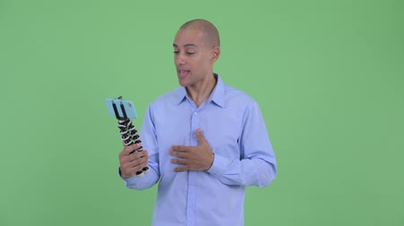 штатив : Happy bald multi ethnic businessman vlogging and showing phone