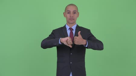 vélemény : Confused bald multi ethnic businessman choosing between thumbs up and thumbs down