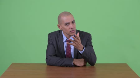 zuřivý : Angry bald multi ethnic businessman talking behind desk
