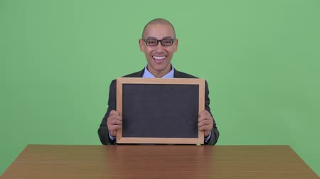 tablica : Happy bald multi ethnic businessman talking while holding clipboard behind desk Wideo