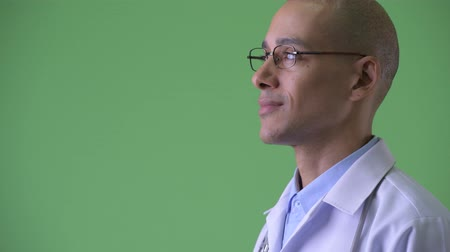 cabeza calva : Closeup profile view of happy bald multi ethnic man doctor smiling Archivo de Video