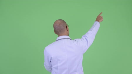 direkt : Rear view of bald multi ethnic man doctor pointing finger Stok Video