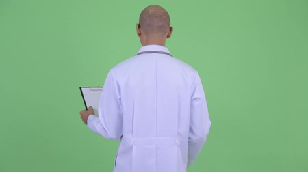 check list : Rear view of bald multi ethnic man doctor thinking and reading on clipboard