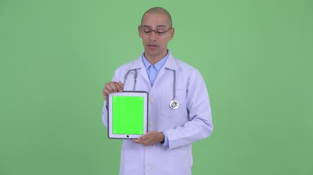 slecht nieuws : Stressed bald multi ethnic man doctor talking while showing digital tablet