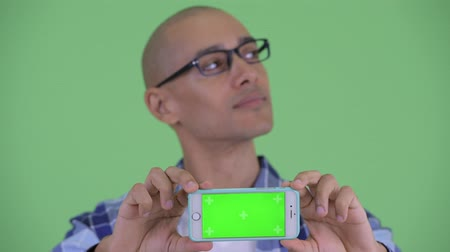 Компьютерщик : Face of happy bald hipster man thinking while showing phone