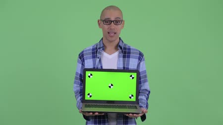 nerd : Happy bald hipster man talking while showing laptop