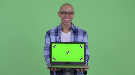 nerd : Happy bald hipster man showing laptop and looking surprised