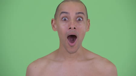 в середине : Face of happy bald multi ethnic shirtless man looking surprised