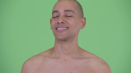 álmodozás : Face of happy bald multi ethnic shirtless man relaxing with eyes closed Stock mozgókép