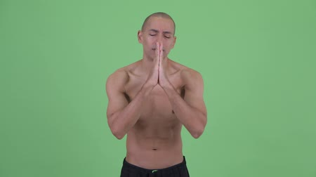 pleading : Bald multi ethnic shirtless man praying Stock Footage