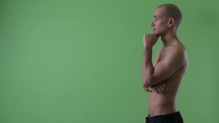 желудок : Profile view of happy bald multi ethnic shirtless man thinking