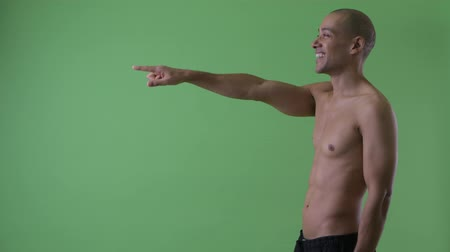 direto : Profile view of happy bald multi ethnic shirtless man pointing finger