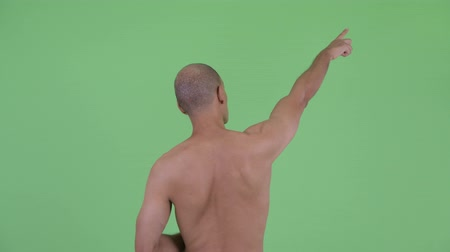 direkt : Rear view of bald multi ethnic shirtless man pointing finger Stok Video