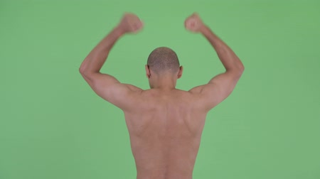 emelt : Rear view of happy bald multi ethnic shirtless man with fists raised