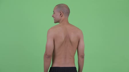 looking far away : Rear view of bald multi ethnic shirtless man thinking and looking around