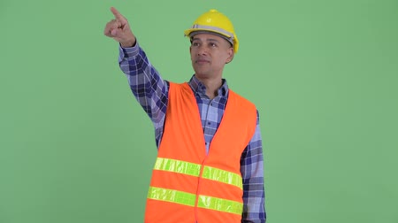 direto : Happy multi ethnic man construction worker pointing finger