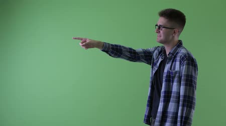 direto : Profile view of happy young hipster man pointing finger Stock Footage