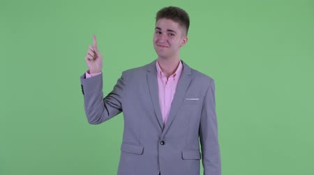 emlékeztető : Happy young businessman pointing up