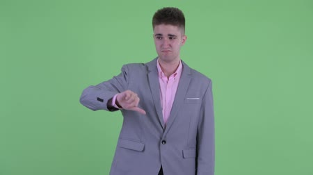 smutek : Sad young businessman giving thumbs down