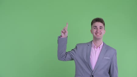 finom : Happy young businessman pointing up and giving thumbs up Stock mozgókép