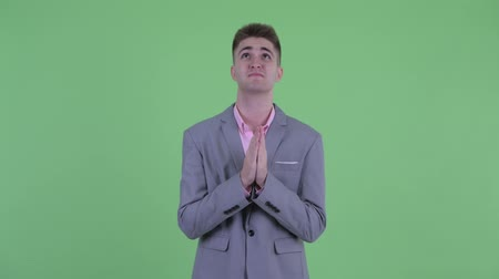 pleading : Young businessman praying and looking up Stock Footage