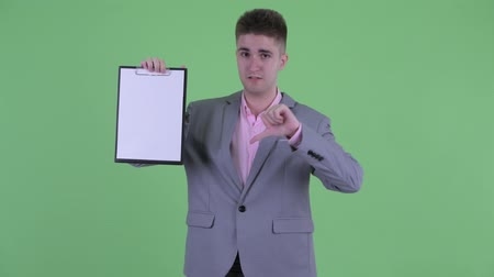 check list : Serious young businessman showing clipboard and giving thumbs down Stockvideo