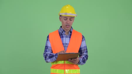 check list : Happy multi ethnic man construction worker talking while holding clipboard
