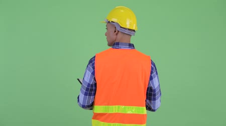 check list : Rear view of multi ethnic man construction worker holding clipboard and looking around Stockvideo