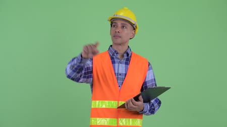 panoya : Happy multi ethnic man construction worker holding clipboard and pointing finger Stok Video