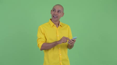 vlogging : Happy handsome bald businessman thinking while using phone Stock Footage