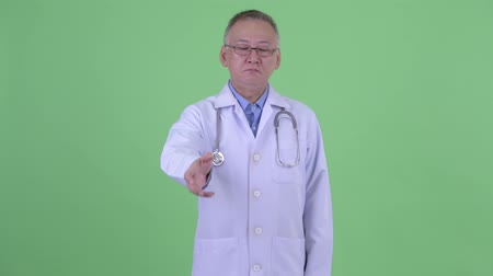 elliler : Mature Japanese man doctor giving handshake