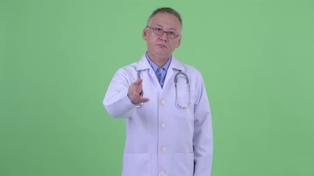 podání ruky : Serious mature Japanese man doctor giving handshake