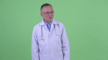 elliler : Happy mature Japanese man doctor looking around