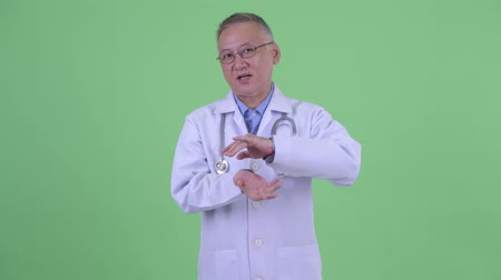 elliler : Happy mature Japanese man doctor being interviewed