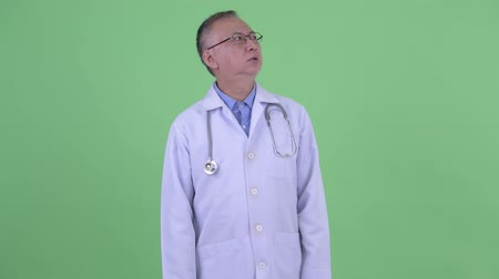 can sıkıntısı : Stressed mature Japanese man doctor looking bored and tired Stok Video