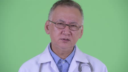elliler : Face of serious mature Japanese man doctor nodding head no