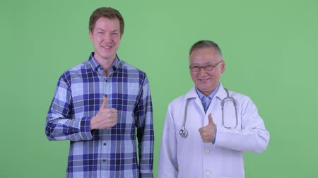 genehmigung : Happy mature Japanese man doctor with young man giving thumbs up together Videos