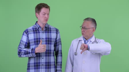 fikirler : Mature Japanese man doctor with young man having different opinions together