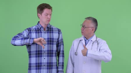 opinion : Mature Japanese man doctor with young man having different opinions together