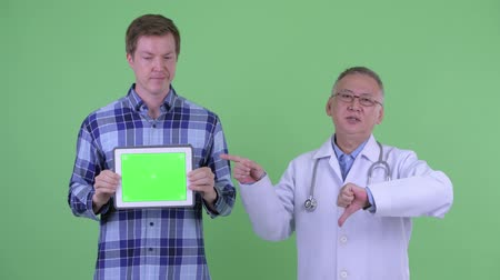 pas d accord : Stressed mature Japanese man doctor with young man showing digital tablet and giving thumbs down Vidéos Libres De Droits