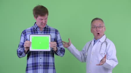 elliler : Shocked mature Japanese man doctor with crazy young man showing digital tablet together Stok Video