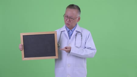 disappointment : Stressed mature Japanese man doctor holding blackboard and giving thumbs down Stock Footage