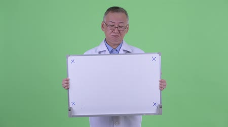 capelli grigi : Stressed mature Japanese man doctor holding white board