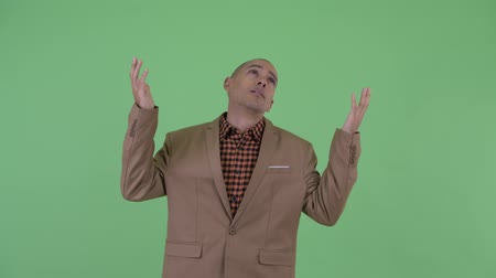 reaching : Tired bald multi ethnic businessman catching something Stock Footage