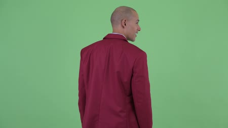 looking far away : Rear view of happy bald multi ethnic businessman looking around