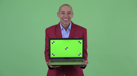 łysy : Happy bald multi ethnic businessman showing laptop and looking surprised Wideo