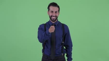 bretels : Happy young bearded Persian businessman pointing at camera