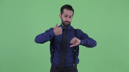 vélemény : Confused young bearded Persian businessman choosing between thumbs up and thumbs down