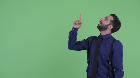 ближневосточный : Happy young bearded Persian businessman pointing up and looking surprised Стоковые видеозаписи