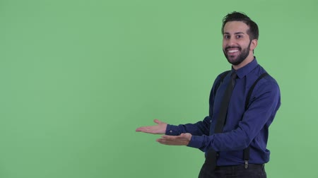 izgatott : Happy young bearded Persian businessman snapping fingers and looking surprised Stock mozgókép